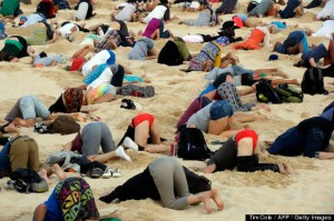 This handout picture taken by Tim Cole and released by 350.org on November 13, 2014 shows Australians burying their heads in the sands of iconic Bondi Beach to send a message to Prime Minister Tony Abbott about the dangers of climate change. As world leaders arrived in the northern city of Brisbane for the G20 summit, more than 100 people dug holes in the famous sand so they could plunge their bodies in halfway, holding their position for three minutes. AFP PHOTO / 350.ORG / TIM COLE ----EDITORS NOTE ---- RESTRICTED TO EDITORIAL USE - MANDATORY CREDIT