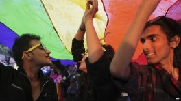 Gay rights activists display a rainbow-colored banner as they march in Delhi.