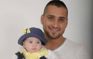 Israeli police officer Zidan Saif holds his baby daughter in a family snapshot. Saif was killed in the line of duty on Nov. 18, 2014.